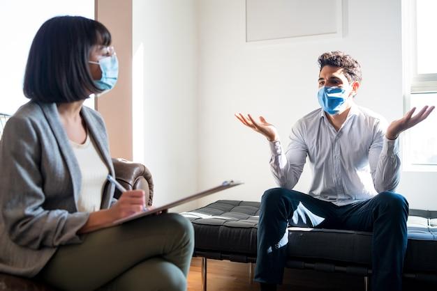 Portret van een psycholoog die met haar patiënt praat en aantekeningen maakt tijdens een therapiesessie