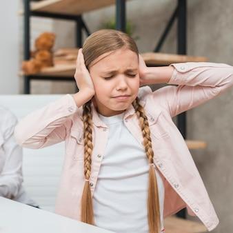 Portret van een radeloos meisje die haar oren behandelen met twee handen