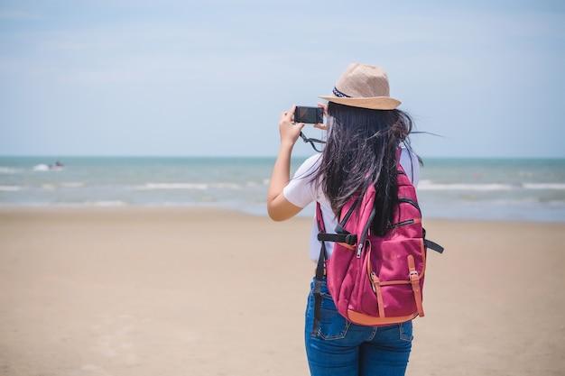 Portret van een reiziger met een camera op het strand