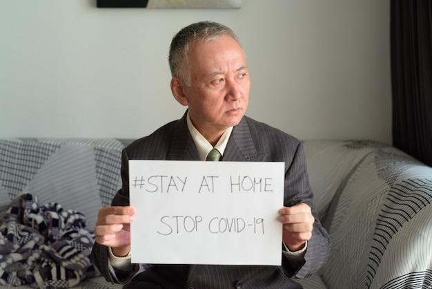 Portret van een rijpe japanse zakenman die thuis blijft in quarantaine voor coronavirus covid-19 pandemie