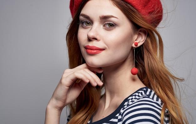 Portret van een romantische vrouw in een lichte de oorbellen gestreepte t-shirt van de make-upbaret