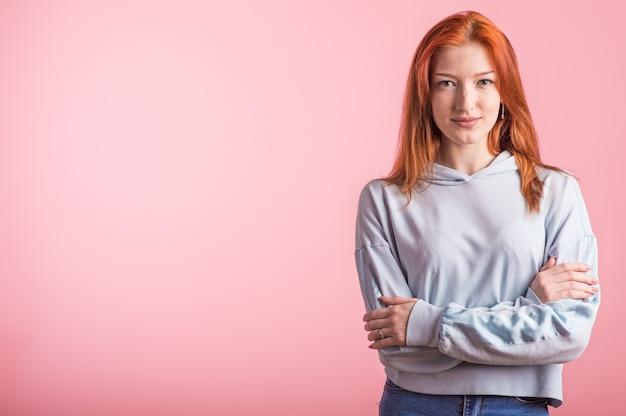 Portret van een roodharig meisje dat haar armen in de studio op een roze achtergrond met copyspace kruiste