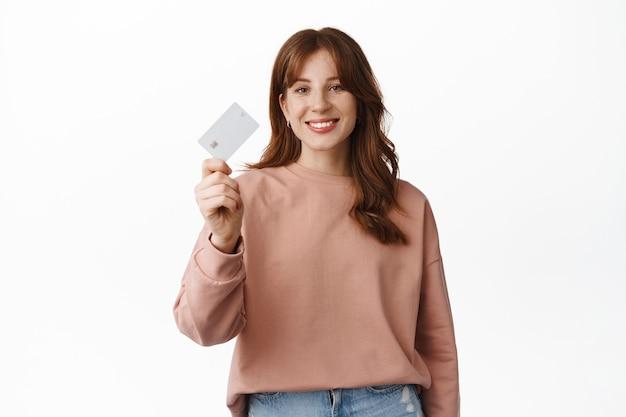 Portret van een roodharig meisje dat lacht, creditcard, reclamebank, speciale aanbiedingen of kortingen toont, verder gaat met winkelen, op wit staat