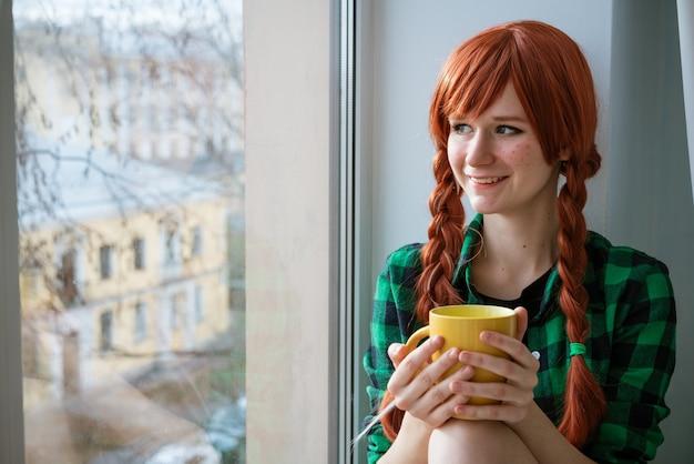 Portret van een roodharig meisje in een groen shirt dat op de vensterbank zit en een gele theemok vasthoudt...