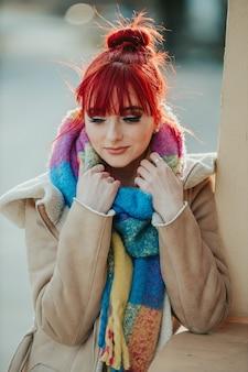 Portret van een roodharig meisje met een pony die haar kleurrijke sjaal vasthoudt