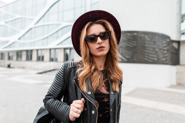 Portret van een roodharige aantrekkelijke jonge hipster vrouw in een elegante hoed in trendy zonnebril in een zwart lederen jas