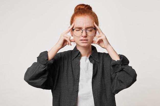 Portret van een roodharige jonge studente gekleed in een zwart herenoverhemd