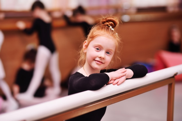 Portret van een roodharige kleine ballerina bij de balletstaaf
