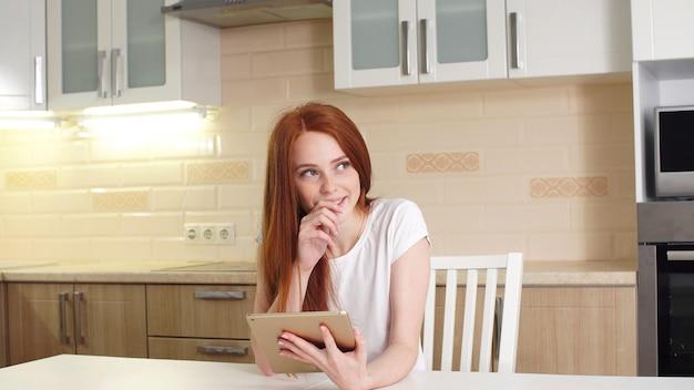 Portret van een roodharige meisje met een tablet-pc in de keuken