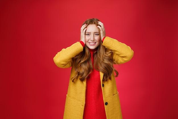 Portret van een roodharige vrouw die in paniek handen vasthoudt tegen het hoofd, tanden op elkaar klemmend en fronsend verbaasd en verontrust, angstig en bezorgd over de rode achtergrond.