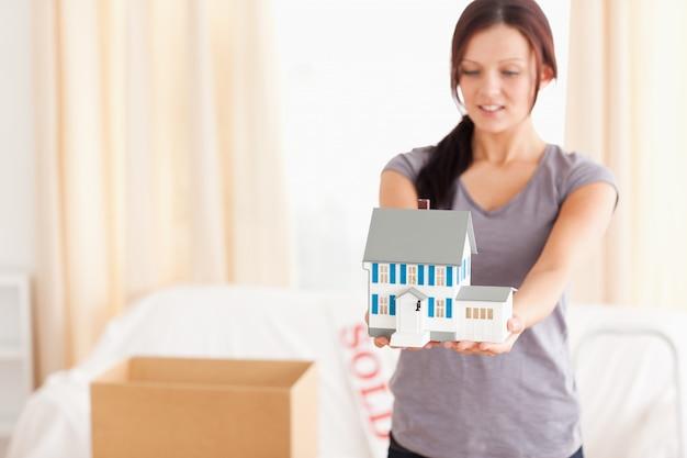 Portret van een roodharige vrouw toont een model huis