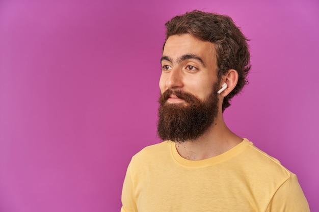 Portret van een rustige, knappe, bebaarde jongeman die opzij kijkt en glimlacht, zelfverzekerd staat, met een koptelefoon op