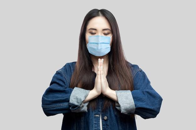 Portret van een rustige, mooie brunette aziatische jonge vrouw met een chirurgisch medisch masker in een blauw spijkerjasje met palmhanden en yoga mediteren. indoor studio opname, geïsoleerd op een grijze achtergrond.