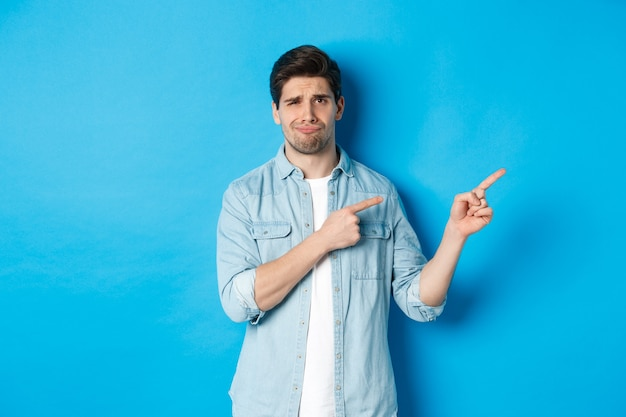 Portret van een sceptische volwassen man die met de vingers naar rechts wijst en grijnst, teleurstelling en twijfel uitdrukt, staande tegen een blauwe achtergrond
