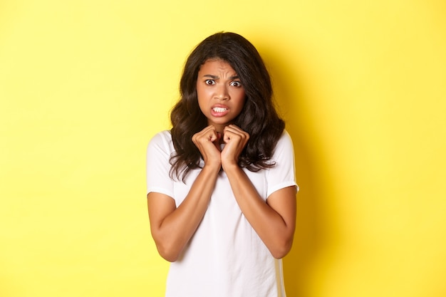 Portret van een schattig afro-amerikaans meisje dat er bang en onwillig uitziet, ontevreden staat