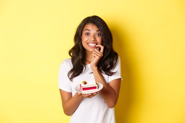 Portret van een schattig afro-amerikaans meisje dat lacht, een heerlijk stuk cake vasthoudt, in de verleiding komt om een toetje te eten, staande over een gele achtergrond