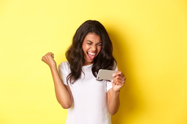 Portret van een schattig afro-amerikaans meisje dat wint in een smartphonespel dat van vreugde schreeuwt en een vuistpomp maakt...