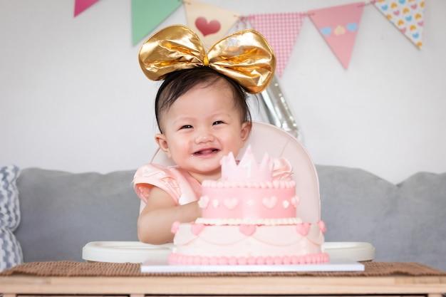 Portret van een schattig aziatisch babymeisje dat haar eerste verjaardag viert met roze prinsescake met geluk.