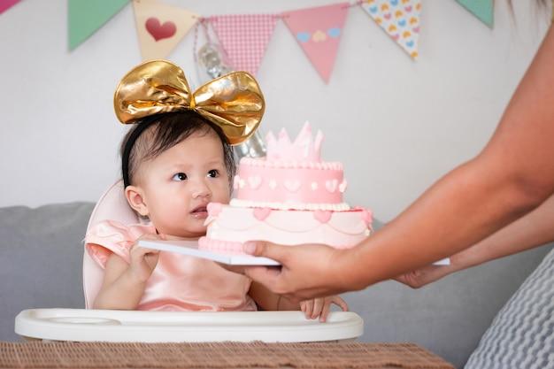 Portret van een schattig aziatisch babymeisje dat haar eerste verjaardag viert met roze prinsescake. ouder die de verjaardagstaart geeft aan haar schattige dochter om haar eerste verjaardag te vieren.