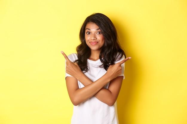 Portret van een schattig besluiteloos afrikaans-amerikaans meisje dat met de vingers zijwaarts wijst en haar schouders ophaalt met het vragen van...