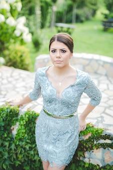 Portret van een schattig brunette bosnisch meisje in een blauwe strakke kanten jurk die buiten in een park staat