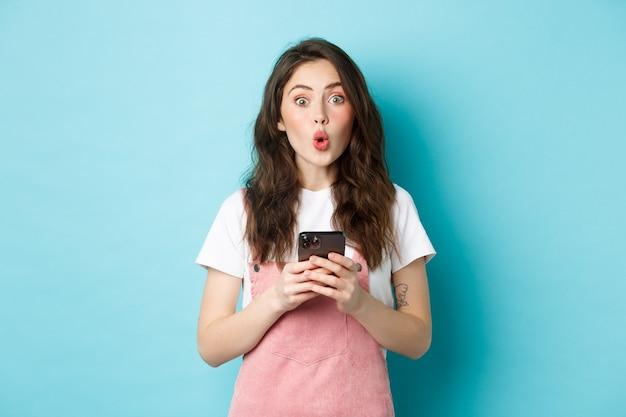 Portret van een schattig brunette meisje kijkt verrast na het gebruik van een smartphone, het vasthouden van een mobiele telefoon en zeg wow op de camera met een onder de indruk gezicht, blauwe achtergrond