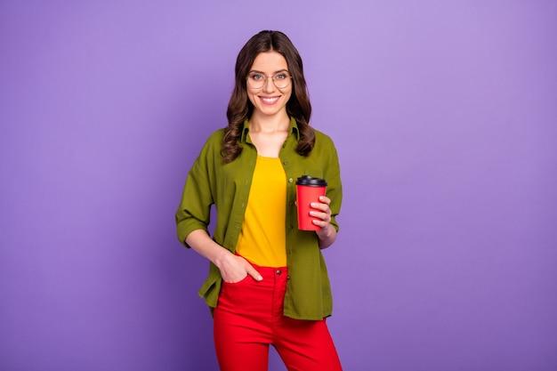 Portret van een schattig charmant mooi middelbare schoolmeisje geniet van de zomer vrije tijd houd de afhaalmaaltijden cappuccino-kop vast, draag een goed uitziende outfit geïsoleerd over een levendige paarse kleur achtergrond