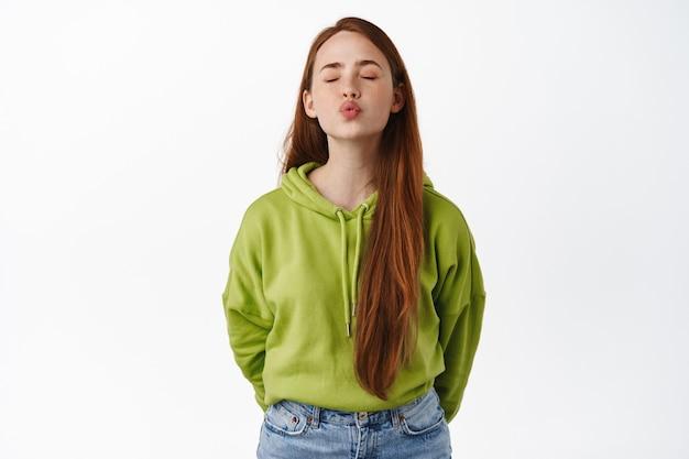 Portret van een schattig en dom meisje met rood haar dat wacht op een kus, sluit de ogen en tuit lippen, kust iemand, voelt zich romantisch, staat op wit