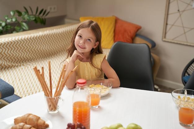 Portret van een schattig en gelukkig klein kaukasisch meisje dat thuis aan de keukentafel zit en heeft