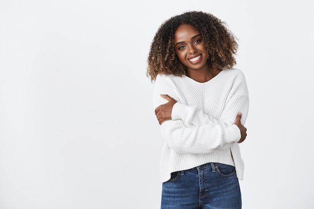 Portret van een schattig en gezellig, goed uitziende, tedere afro-amerikaanse vrouw met krullend haar die haar hoofd kantelt en zichzelf knuffelt met gekruiste handen omdat ze zich kil of koud voelt