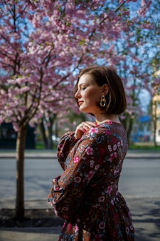 Portret van een schattig en mooi vrouwenmeisje in een jurk in de tuin in het midden van bloeiende sakura. lente en zon tijd. onscherpe achtergrond en geselecteerde focus.