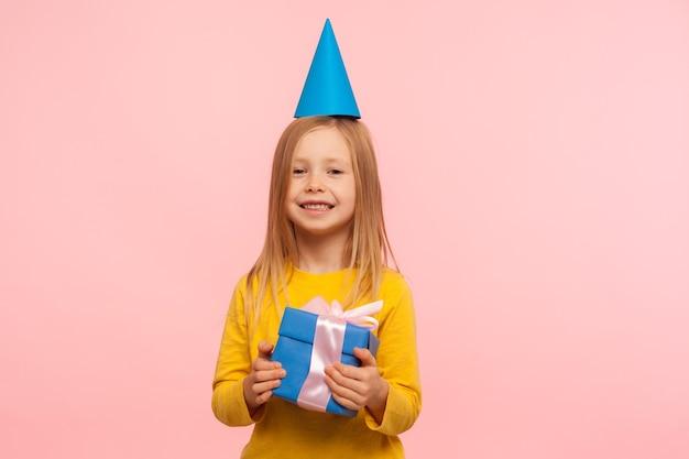 Portret van een schattig gelukkig klein meisje met een grappige feestkegel op het hoofd die een geschenkdoos vasthoudt en vrolijk lacht naar de camera, enthousiast over het verjaardagscadeau. indoor studio-opname geïsoleerd op roze achtergrond