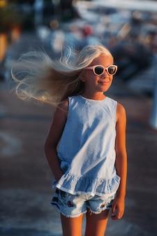 Portret van een schattig glimlachend tien-jarig meisje met bril. een meisje in korte broek en een blauw t-shirt bij zonsondergang in de buurt van de zee. turkije.