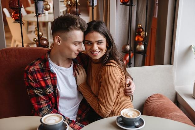 Portret van een schattig jong gelukkig liefdevol paar zittend in café binnenshuis knuffelen.