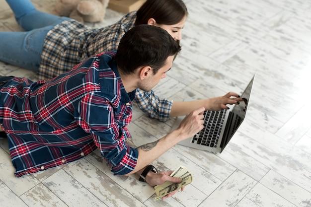 Portret van een schattig jong stel dat thuis op de vloer ligt en het budget beheert met behulp van een laptop
