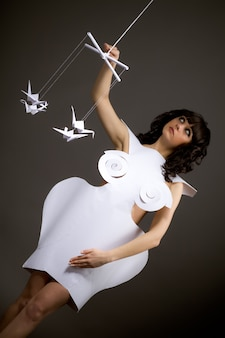 Portret van een schattig jong verdrietig meisje in origami jurk met bewegende armen als een marionet die vliegende papieren vogels op een zwarte achtergrond aanraakt