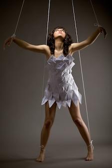 Portret van een schattig jong verdrietig meisje in origami jurk met bewegende armen als een pop op een zwarte achtergrond