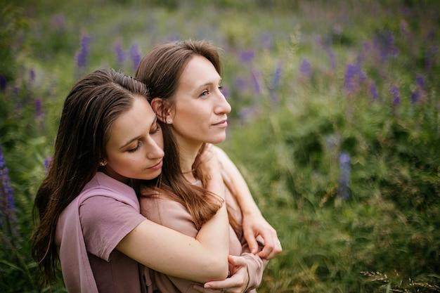 Portret van een schattig kaukasisch brunette lesbisch koppel knuffelen op het veld met wilde lupines