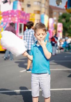 Portret van een schattig kind dat suikerspin eet op een achtergrond van een zomers eerlijk festival