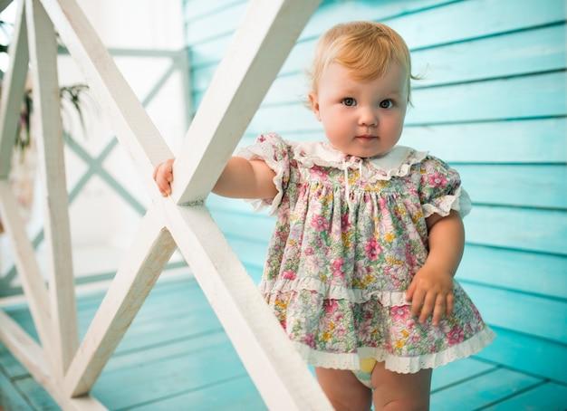 Portret van een schattig klein blond meisje in een gebloemde jurk staande op de veranda van een houten huis.
