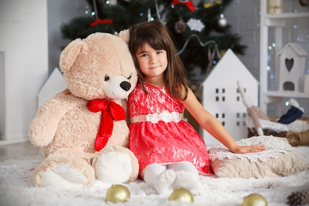 Portret van een schattig klein brunette meisje knuffelen een zachte teddybeer in interieur met kerstversiering