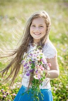 Portret van een schattig klein gelukkig zevenjarig meisje met lupine bloemen in een veld in de natuur buiten.