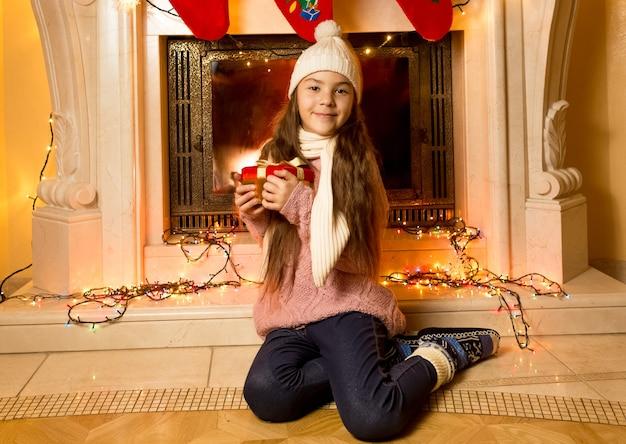 Portret van een schattig klein meisje dat bij de open haard zit met een kerstcadeau
