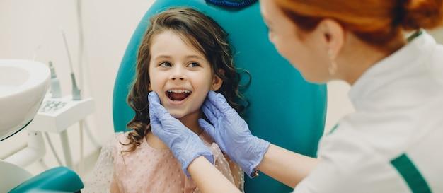 Portret van een schattig klein meisje dat haar tanden toont aan haar pediatri-stomatoloog voordat ze een tandoperatie doet.