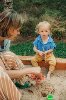 Portret van een schattig klein meisje dat in de zandbak zit