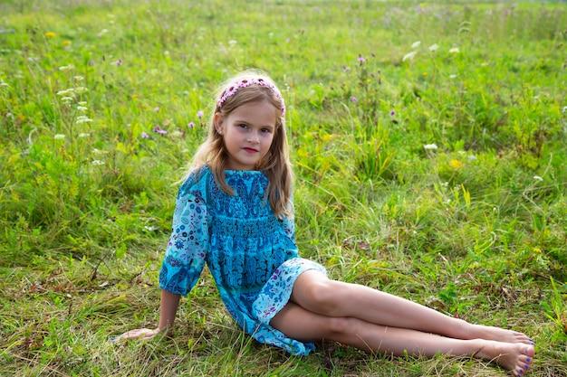 Portret van een schattig klein meisje dat in een weiland ligt. mooi meisje 7-9 jaar oud met krullend blond haar in een jurk en blote voeten