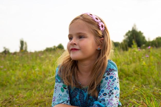 Portret van een schattig klein meisje dat in een weiland ligt. mooi meisje 7-9 jaar oud met krullend bruin haar.