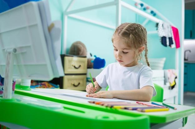 Portret van een schattig klein meisje dat naar de camera kijkt en glimlacht terwijl ze foto's maakt of huiswerk maakt, aan een tafel in het interieur zit, ruimte kopieert