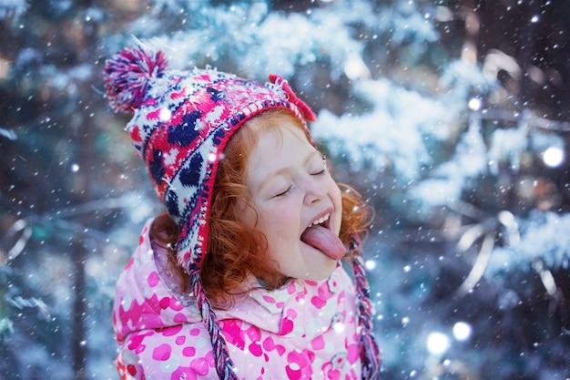 Portret van een schattig klein meisje dat sneeuwvlokken mond vangt