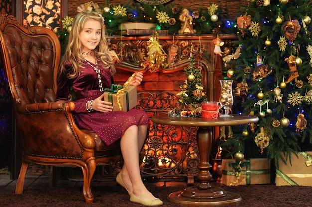 Portret van een schattig klein meisje in de buurt van een versierde kerstboom